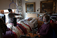Dr David Binnie visiting patient Georgina Hobhouse at her home on the the Inner Hebridean island of Colonsay on Scotland's west coast.  The island is in the council area of Argyll and Bute and has an area of 4,074 hectares (15.7 sq mi). Aligned on a south-west to north-east axis, it measures 8 miles (13 km) in length and reaches 3 miles (4.8 km) at its widest point, in 2019 it had a permanent population of 136 adults and children.