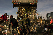 """A garbage truck disposes trash at """"El Volcadero"""" garbage dump in Paraná, Province of Entre Rios, Argentina, on May 4, 2019. The habitants of the shantytown situated next to the dump search the garbage for food, clothes and valuable materials such as paper, carton, glass, plastic and others. Photo: Sarah Pabst for The New York Times"""