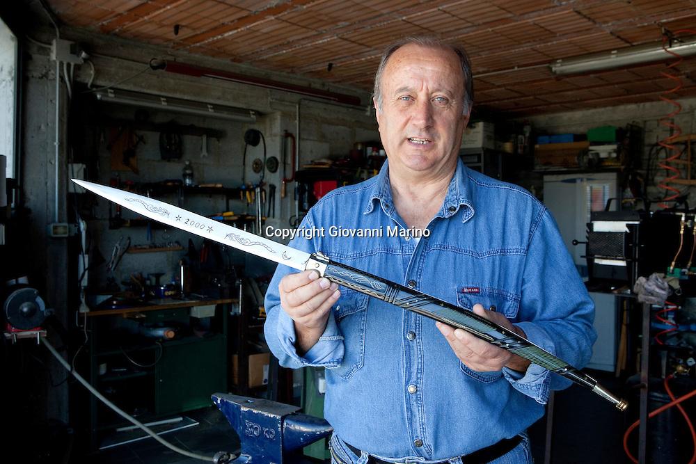"""Avigliano (PZ), 04-10-2010 ITALY - Vito Aquila, artigiano di Balestre. Il coltello di Avigliano, comunemente conosciuto come """"balestra"""", impreziosito con decorazioni in argento e ottone che le conferivano un certo valore non solo artistico,ha identificato per tutto l'Ottocento e parte del Novecento il carattere fiero e risoluto del popolo aviglianese, come attestato in una lunga casistica di riscontri documentari. La """"balestra"""" è un'arma a tutti gli effetti, ed è già considerata -nell'ambito delle manifatture di ferro - oggetto di pregio. Per l'approvvigionamento dell'argento e dell'ottone destinati alla decorazione del manico del coltello gli armieri si rivolgevano agli orefici o agli ottonari. La """"balestra"""" era un'arma del popolo, pronta ad essere impiegata, a seconda delle circostanze, per la difesa o l'offesa tanto dagli uomini quanto dalle donne. Queste, la ricevevano come regalo di fidanzamento dal rispettivo promesso sposo per meglio difendere il proprio onore, perpetrando un'usanza molto sentita almeno fino ai primi decenni del '900..Nella Foto: Vito Aquila mostra la grande balestra forgiata per il millennio."""