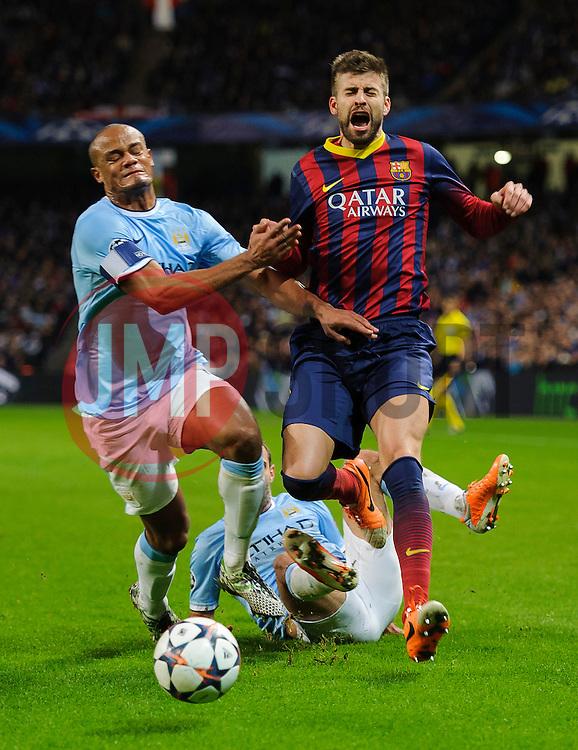 Barcelona Defender Gerard Pique (ESP) is tackled by Man City Defender Pablo Zabaleta (ARG) and Defender Vincent Kompany (BEL) - Photo mandatory by-line: Rogan Thomson/JMP - Tel: 07966 386802 - 18/02/2014 - SPORT - FOOTBALL - Etihad Stadium, Manchester - Manchester City v Barcelona - UEFA Champions League, Round of 16, First leg.