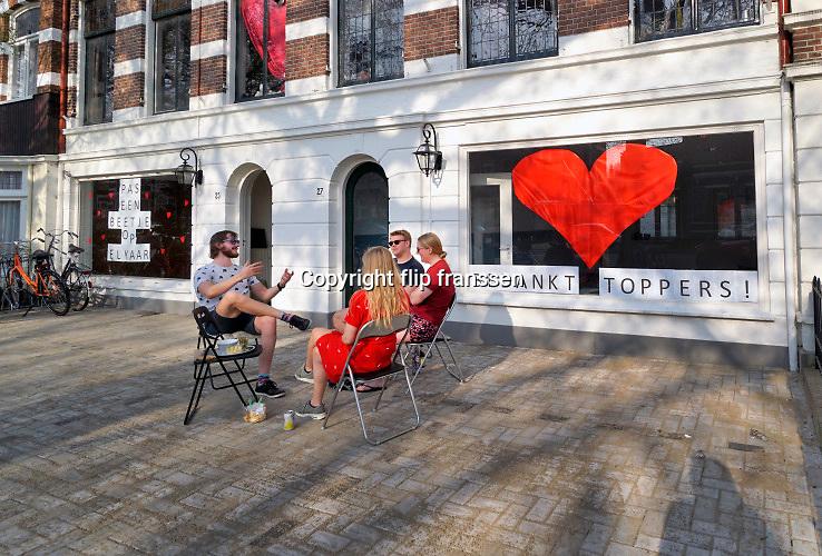 Nederland, Nijmegen, 12-4-2020  Bewoners van een studentenhuis, een huishouden dus, zitten buiten bij elkaar in de zon op deze 1e, eerste paasdag. Op de begane grond bevindt zich een kantoor wat een dankbetuiging aan de medewerkers in de zorg op het raam heeft geplakt.Foto: Flip Franssen