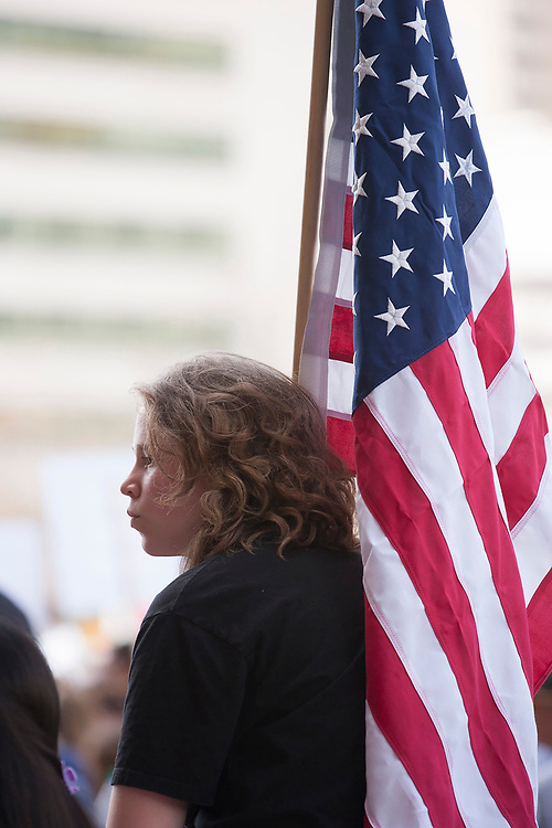 A student holding an American flag listens to speakers durng the March for Our Lives in front of Dallas City Hall in downtown Dallas.