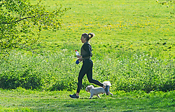 ©Licensed to London News Pictures 21/04/2020  <br /> Sidcup, UK. A young lady running with her dog. A sunny morning at Foots Cray Meadows in Sidcup, South East London as people get out of the house from coronavirus lockdown to exercise. Photo credit:Grant Falvey/LNP