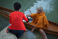 Thai Monk Collecting Alms -  Most activities are carried out on the Mae Klong River or the connecting canals in the Amphawa area. This includes monks traveling from temple to temple, and collecting alms on the morning rounds. The respect given by a lay Buddhist to a Buddhist monk or nun is not charity as presumed by Westerners but it is closer to a symbolic connection showing humility and respect. The presence of so Buddhist monks is a stabilizing influence in Thai society and the act of alms giving assists in connecting lay people to the monk and what he represents.