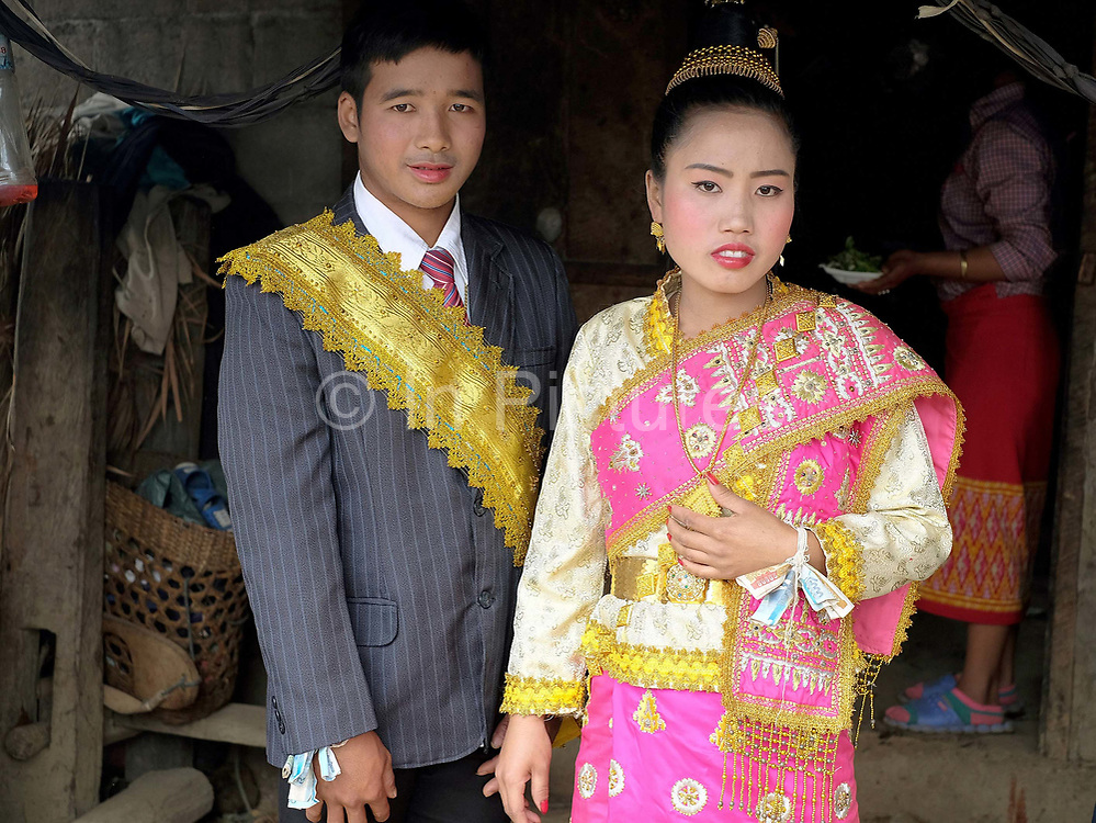 An Akha couple dressed in Lao style clothing at their wedding in Luang Namtha province, Lao PDR.