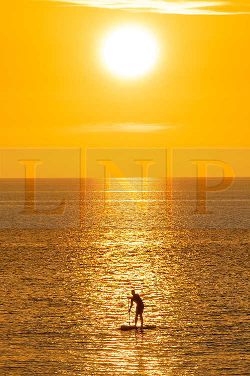 ©Licensed to London News Pictures. 19/09/2019 Aberystwyth UK.<br /> The sun setting gloriously over  Cardigan Bay silhouettes a man paddle boarding on the sea at the end of a day of unbroken clear blue skies and warm September sunshine in Aberystwyth, west Wales.   as the 'indian summer' mini heat-wave continues over much of the souther parts of the UK.Photo credit Keith Morris/LNP