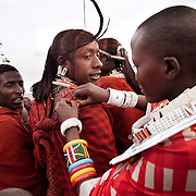 Wilson's wedding day...A young female admirer of the dancing young men is fixing his clothes which has come loses during the jumping. ..It is mainly Maasais who live in the Loita Hills up above the Serengeti plains. They live in small villages and communities called bomas and live mainly of raising and selling live stock such as cattle and goats. Its a very remote region in Kenya, hard to get to without a four wheel drive with very little infrastructure and up till 2010 no mobile phone network. The Maasais are well known though out Kenya and the world for their colorful clothing and their way of keeping their old traditions alive.
