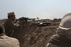 20/10/2016. Bashiqa, Iraq. A Kurdish peshmerga fighter fires a PKM machine gun at Islamic State positions during an offensive to retake a large area around the ISIS held town of Bashiqa, Iraq, today (20/10/2016).<br /> <br /> Launched in the early hours of today with support from coalition special forces and air strikes, the attack is part of the larger operation to retake Mosul from the Islamic State, and involves both the Kurds and the Iraqi Army. The city of Bashiqa, around 9 miles north of Mosul, is one of several gateway areas that must be taken before any attempted offensive on Mosul itself.<br /> <br /> Despite the peshmerga suffering several casualties after militants fought back using mortars, heavy machine guns and snipers, the Kurdish forces were quickly taking ground with Haider al-Abadi, the Iraqi prime minister, stating that the operation to retake Mosul was progressing faster than expected. Photo credit: Matt Cetti-Roberts/LNP