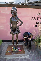© Licensed to London News Pictures. 23/07/2021. LONDON, UK.  A man views floral tributes next to the statue of statue of Amy Winehouse by sculptor Scott Eaton in Stables Market in Camden Town on the tenth anniversary of the late singer's death.  Photo credit: Stephen Chung/LNP