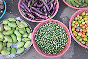 Fresh fruit and vegetables including mangoes, aubergines/egg plant and tomatoes for sale at Daeum Kor morning market in Phnom Penh, the capital city of Cambodia. A large variety of local products are available for sale in fresh markets all over Cambodia, all being sold on small individual stalls.