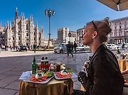 A young lady enjoys a lunch on the Piazza del Duomo in Milan, Italy. Piazza is the living heart of Milan with a unique atmosphere.