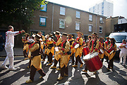 Hackney carnival 2014. The procession started in Ridley Road and passed by the The Hackney Town Hall with thousands of spectators lining the road.<br /> A band of musicians dressed in brown and golden shirts make their way down Richmond Road