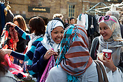 Muslim girls laugh and joke with one another at a scarf stall in Spitalfields Market, London.