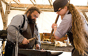 USA, Alaska,Ketchikan, Blacksmiths' Jake Beimler and Krystle DeCourcey working hot iron into pieces of art in their open air shop in downtown Ketchikan