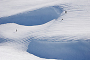 Three skiers and a snowboarder survey the landscape on an off-piste trail at ski field Turoa. Turoa is located on active volcano Mount Ruapehu, New Zealand.