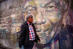 """South Africa - Cape Town - 17 June 2020 - Man walk past a Mural of Nelson Mandela as we celebrate Mandela Day tomorrow. Nelson Mandela International Day (or Mandela Day) is an annual international day in honour of Nelson Mandela, celebrated each year on 18 July, Mandela's birthday. The day was officially declared by the United Nations in November 2009. Picture"""" Brendan Magaar/African News Agency(ANA)"""