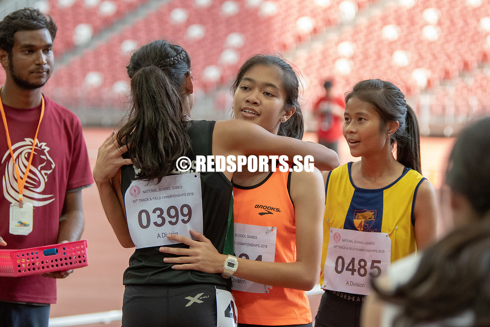 A Division Girls' 4x100m final runners briefly embrace after the race. (Photo X © REDintern Jared Khoo)