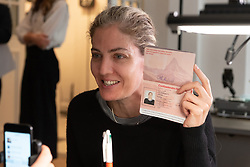 """© Licensed to London News Pictures. 05/10/2018. London, UK. A visitor has their Swiss passport produced at the Tom Sachs art installation titled Swiss Passport Office.  The 24hliveperformanceSwiss Passport Office is on show at the Galerie Thaddaeus Ropac. Those wishing to purchase a passport will be photographed and have their name hand-typed onto a serial-numbered passport issue, stamped with a Studio endorsement and entered into the permanent database. Passports cost €20 (no British pounds will be accepted). Swiss Passport Officeencompasses contemporary concerns relatingto Brexit, Syria and Trump's immigration policies and their challenge to the notion of global citizenship. """"To effect change, we must first imagine the world not the way it is, but the way we want it to be,"""" Sachs says. Photo credit: Ray Tang/LNP"""