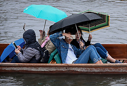© Licensed to London News Pictures. 10/08/2018. Cambridge, UK.  Despite the rain, international tourists take part in punting on the River Cam in Cambridge.  The fall in the value of Sterling has seen an influx of tourists visiting many popular landmarks in the UK, taking advantage of cheaper prices.  Photo credit: Stephen Chung/LNP