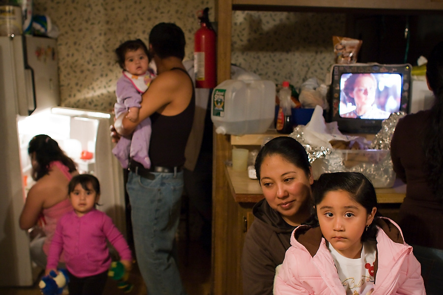 People crowd into a neighbor's house to begin celebrating the Fiesta de la Hispanidad, commemorating the coronation of the Virgen de Guadalupe as queen of the hispanic world at Hudson Valley Foie Gras in Ferndale, New York on October 11, 2008. Some of the workers and their families, practically all Mexican immigrants, live on the grounds of the factory in company provided housing; a small, isolated Mexican community flourishes in the Catskills.