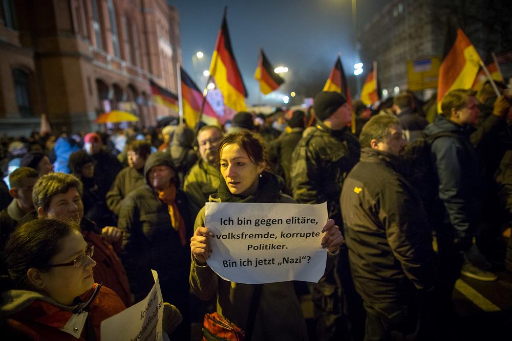 """Mehrere tausend Menschen protestieren in Berlin gegen eine BÄRGIDA - Demonstration, einen Ableger des islamfeindlichen Dresdner Bündnisses """"Patriotischer Europäer gegen Islamisierung des Abendlandes"""" - PEGIDA. Die ca. 400 Teilnehmer der rechten Demonstration waren von Gegendemonstranten umgeben, wegen der Blokaden der Demonstrationsroute wurde die Veranstaltung abgebrochen. Pegida-Anhängerin mit Schild: Ich bin gegen elitäre, volksfremde, korrupte Politiker. Bin ich jetzt """"Nazi""""?<br /> <br /> [© Christian Mang - Veroeffentlichung nur gg. Honorar (zzgl. MwSt.), Urhebervermerk und Beleg. Nur für redaktionelle Nutzung - Publication only with licence fee payment, copyright notice and voucher copy. For editorial use only - No model release. No property release. Kontakt: mail@christianmang.com.]"""