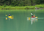Colorful kayakers ply the Chilkoot Lake near Haines, Alaska. PLEASE CONTACT US FOR DIGITAL DOWNLOAD AND PRICING.