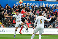 Southampton's Shane Long (c) beats Swansea's Neil Taylor (l) to a header. Barclays Premier league match, Swansea city v Southampton at the Liberty Stadium in Swansea, South Wales on Saturday 13th February 2016.<br /> pic by  Carl Robertson, Andrew Orchard sports photography.