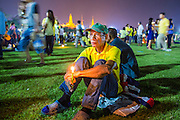 05 DECEMBER 2012 - BANGKOK, THAILAND:  A man sits alone on the field at Sanam Luang after the public ceremony to celebrate the birthday of Bhumibol Adulyadej, the King of Thailand, on Sanam Luang, a vast public space in front of the Grand Palace in Bangkok Wednesday night. The King celebrated his 85th birthday Wednesday and hundreds of thousands of Thais attended the day long celebration around the Grand Palace and the Royal Plaza, north of the Palace. The Thai monarch is revered by most Thais as unifying force in Thailand's society, which is not yet recovered from the political violence of 2010.     PHOTO BY JACK KURTZ