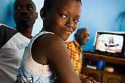 Solange Djaha Ahou, 8, sits on the lap of HIV/AIDS counselor Kevin Kouassi Gallet during a home visit in Dimbokro, Cote d'Ivoire on Friday June 19, 2009. At right is Solange's father Barthelemy Djaha N'Gueran. Both are HIV-positive.