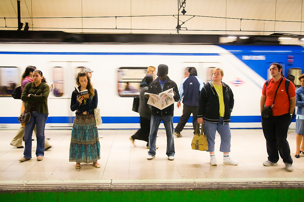 People wait at a subway station platform while a train passes behind them in the metro in Madrid, Spain.