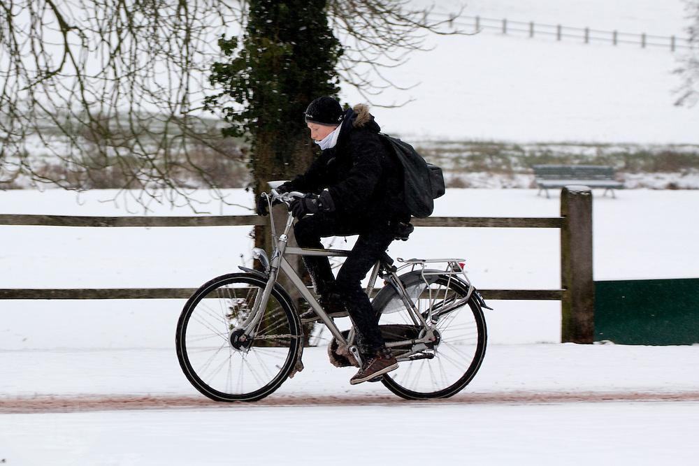 Geconcentreerd rijdt een jongen op de Zijpendaalseweg in Arnhem door de sneeuw.<br /> <br /> Concentrated a boy is cycling at the Zijpendaalseweg in Arnhem in the snow.