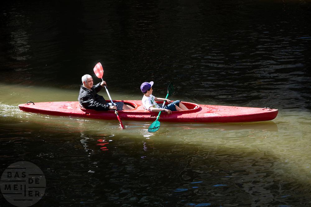 Een man vaart met een jongen in een kano door de Oudegracht in Utrecht.<br /> <br /> A man in canoeing in Utrecht.