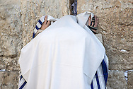 A man fully covered in a tallit shawl, with an arm tefillin wrapped on his right hand prays in a crevice of the Western Wall. The tallit is worn over the outer clothes during the morning prayers (Shacharit). The tallit has special twined and knotted fringes known as tzitzit attached to its four corners. The Bible does not command wearing of a unique prayer shawl or tallit. Instead, it presumes that people wore a garment of some type to cover themselves and instructs them to add fringes (tzitzit) to the 4 corners of these . The exact customs regarding the tying of the tzitzit and the format of the tallit are of post-biblical, rabbinic origin and can vary between various Jewish communities.