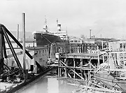 """9904-B04F. """"Albina Engine & Machine Works Inc. barge launching and other pix, ran November 5, 1950"""" caption published in Oregonian November 5, 1950 pg. 25: """"Shipbuilding workers at Albina Engine & Machine Works took time out Friday to launch this steel 138-foot hog fuel barge for Western Transportation company. Keel was laid October 5. The bin, 10 feet high, has capacity for 275 units. Work was started immediately on another barge of similar size and capacity."""" (A/C similar shots, A was published. D is barge in river. E/F is Albina shipyard.)"""