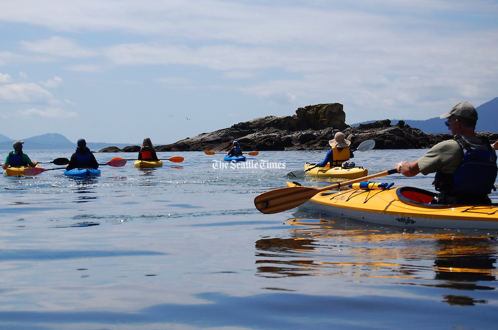 Kayakers, leaving Wildcat Cove in Larrabee State Park, view Gargoyle Rock, which leads to Chuckanut Bay and Chuckanut Island near Bellingham.<br />