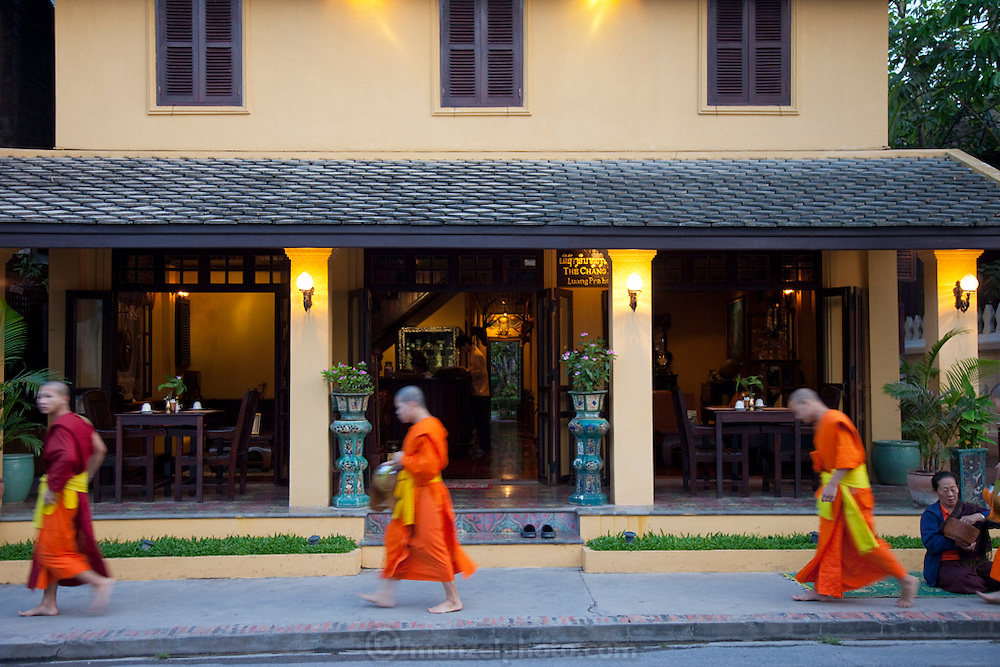 Luang Prabang, Laos. Every morning at dawn, Buddhist monks walk down the streets collecting food alms from devout, kneeling Buddhists, and some tourists. They then return to their temples (also known as wats) and eat together. This procession is called Tak Bat, or Making Merit. Here they pass by the Chang Guest House.