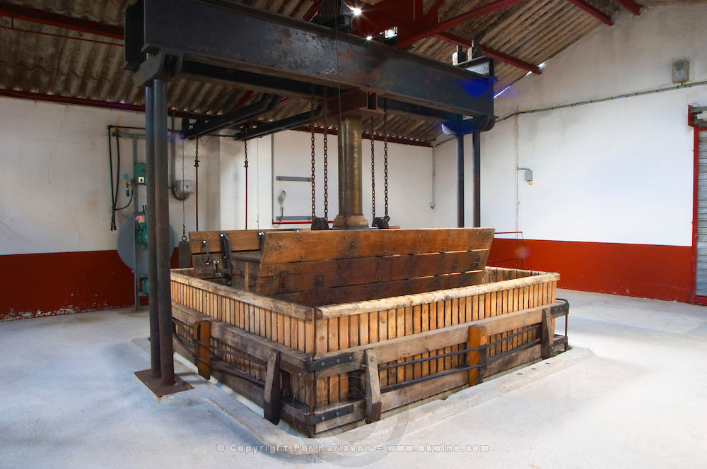In the winery: a traditional, square, vertical, basket wine press with the hydraulic machinery in the background, Champagne Jacquesson in Dizy, Vallee de la Marne, Champagne, Marne, Ardennes, France