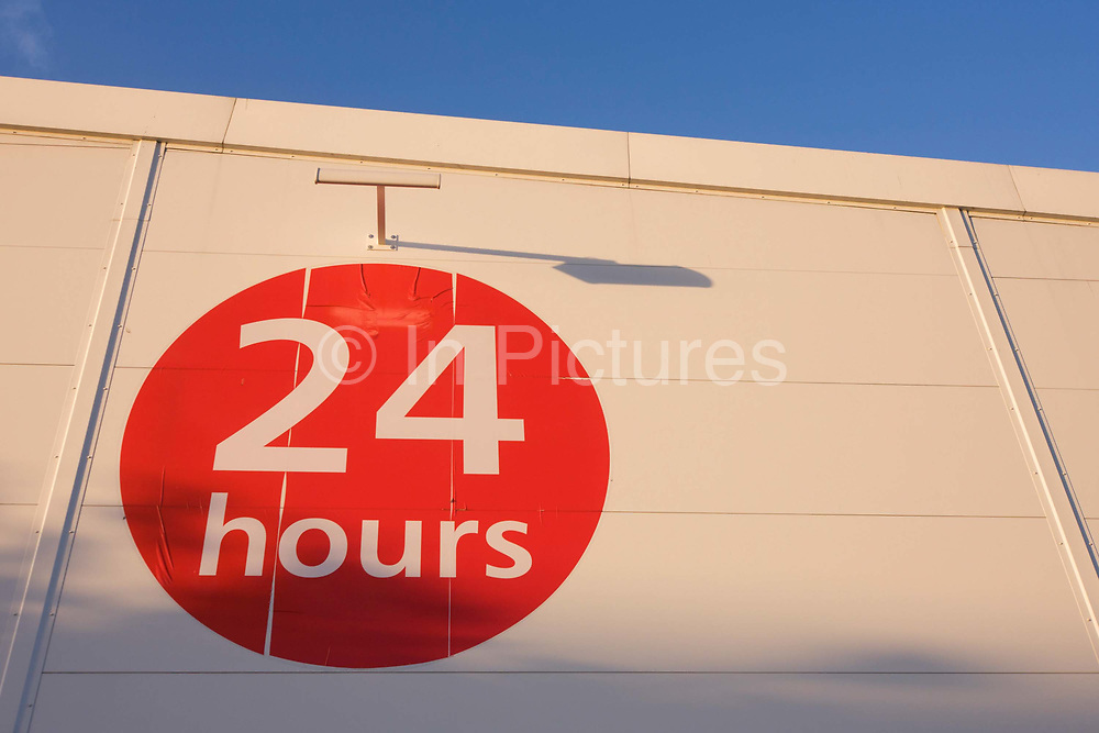 Red circular sign telling shoppers that supermarket is open 24 hours a day and night. Looking up from below from the retail car park, we see the round sign in late afternoon winter sunlight. The warehouse walls rise up in a powerful and influential angle and show the large numbers saying 24 and in letter the word hours in lower-case. The Sunday Trading Act 1994 is an Act of Parliament in the United Kingdom governing the right of shops in England and Wales to trade on a Sunday. Buying and selling on Sunday had previously been illegal, with exceptions, under the Shops Act 1950. Large retail park shops usually open 11am-5pm, with supermarkets more usually choosing 10am-4pm.