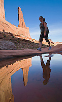 """A woman hiking """"Broadway"""" in Arches National Park, Utah, USA."""