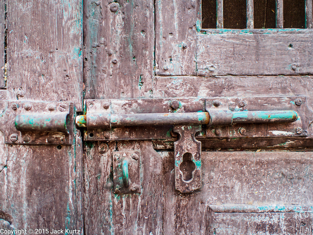 17 MARCH 2015 - BANGKOK, THAILAND: A detail photo of a doorway with a deadbolt on it at the old Customs House in Bangkok. The old Customs House was once the financial gateway to Thailand (before 1932 called Siam). It was designed by an Italian architect in the 1880s. In the 1950s, customs moved to new, more modern building and the Customs House became the headquarters for the Marine firefighters. The firefighters now live in the decrepit buildings with their families.    PHOTO BY JACK KURTZ