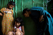 Rubina Ali, 9, the child actor playing the role of 'young Latika', the friend/lover of Jamal, protagonist of Slumdog Millionaire, the famous movie winner of 8 Oscar Academy Awards in December 2008, is playing with her mobile phone while two friends overlook, inside the slum where she still lives with her family next to the train station of Bandra (East), Mumbai, India. Various promises were made to lift the two young actors (Azharuddin Ismail and Rubina Ali) from poverty and slum-life but as of the end of May 2009 anything is yet to happen. Rubina's house was recently demolished with no notice as it lay on land owned by the Maharashtra train authorities and she is now permanently living with her uncle's family in a home a stone-throw away in the same slum. Azharuddin's home too was demolished in the past two weeks, as it happens every year in his case, because the concrete walls were preventing local authorities to clear a drain passing right behind it. As usual, his father is looking into restoring the walls as soon as the work on the drain has been completed.