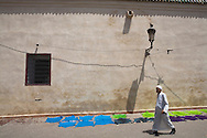 Man walking past colorfully dyed skins, Marrakesh, Morocco