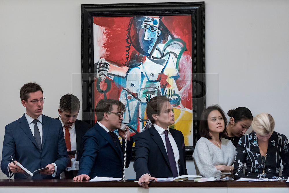 """© Licensed to London News Pictures. 01/03/2017. London, UK. Sotheby's staff, bidding on behalf of telephone clients, stand in front of """"Femme Nue Assise"""" by Pablo Picasso which sold for a hammer price of GBP12m (est. GBP9.5-12.5m) at the evening sale of Impressionist and Surrealist Art at Sotheby's in New Bond Street. Photo credit : Stephen Chung/LNP"""