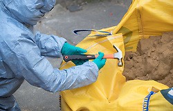 © Licensed to London News Pictures.19/03/2017.London, UK. A police forensics officer examines a hammer found in a builder's bag of sand round the corner from a property on Wilberforce Road where one baby has been found dead and another seriously injured in Finsbury Park. Police have named  Bidhya Sagar Das who lives at the property and is wanted in connection with the death.  Photo credit: Peter Macdiarmid/LNP