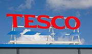 Sign for Tesco supermarket store against blue sky, Calne, Wiltshire, England, UK