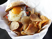 Closeup of an Eggsquisite Burger -- an over-easy egg on a bun topped with onion straws and bacon bits, plus a side of home-made potato chips.