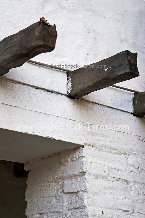 Two wooden rail road beams protruding out of a whitewashed building, Architecture, California USA. Today these beams are known to contain high concentration of insecticides and poisonous heavy metals used to cure and protect the wood