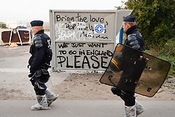 """French police officers patrol near a large crew of demolition workers who have started to break down living areas of the """"Jungle"""" migrant camp, close to Calais in northern France."""