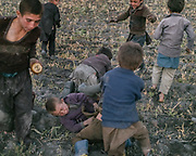 Kids fight in a field.<br /> The traditional life of the Wakhi people, in the Wakhan corridor, amongst the Pamir mountains.