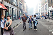 Local workers leave the area. A fire broke out on Dean Streen in Soho, Central London on Friday afternoon. The fire, in a five storey building in the heart of the city raged with firefighters struggling to get the blaze under control. In the nearby streets workers finishing early stood in the smoke filled streets having an end-of-the-week beer in the ghostly atmosphere.